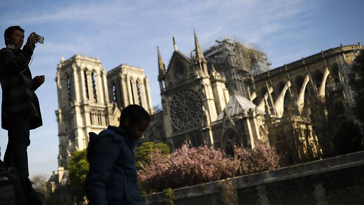 Ein Tourist macht am Mittwoch ein Foto von Notre Dame - Frankreichs Kabinett beriet gleichentags über den Wiederaufbau nach dem Brand der Kathedrale.