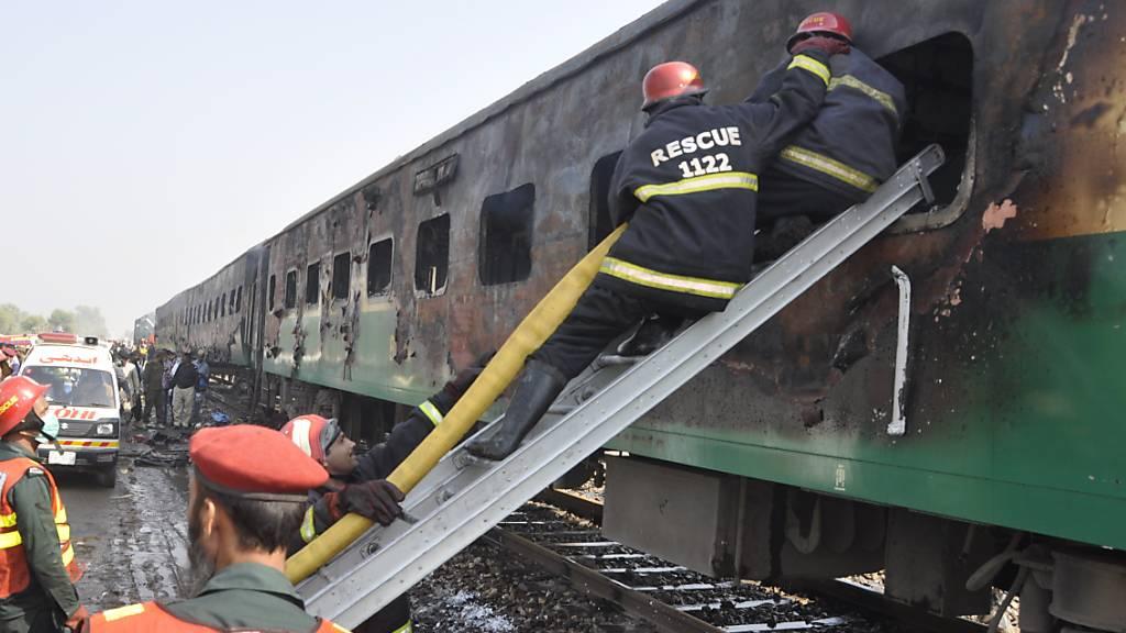 Rettungskräfte suchen nach Überlebenden des Brandes im Zug.