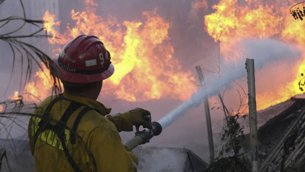 Ein Feuerwehrmann versucht, die Flammen an einem brennenden Haus in Lytle Creek zu löschen, während das «South Fire» brennt. Foto: Ringo H.W. Chiu/AP/dpa