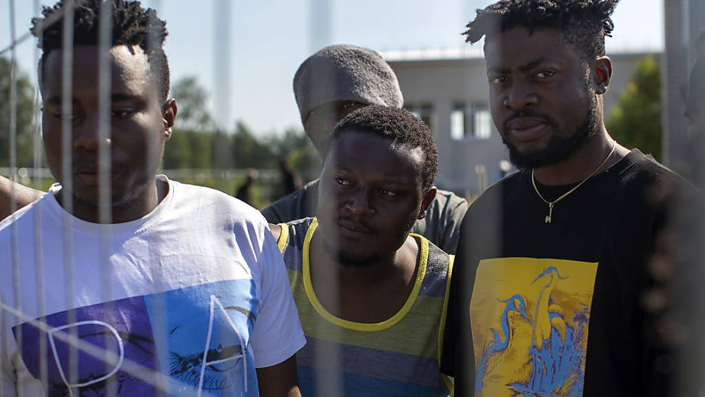 ARCHIV - Migranten aus Kamerun stehen am Zaun eines Flüchtlingslagers. Litauen hat angesichts einer stark steigenden Zahl illegal Einreisender mit dem Bau eines Zauns an der Grenze zu Belarus begonnen. Foto: Mindaugas Kulbis/AP/dpa