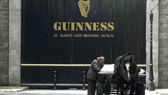 Mann mit Pferdekutsche vor der Guinness-Brauerei St. James Gate in Dublin. (Archivbild)