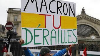 """""""Macron, du spinnst"""" heisst es auf einem Protestschild vor der Gare de l'Est  in Paris - in einem Wortspiel mit """"le rail"""", deutsch: """"die Schiene, das Gleis""""."""