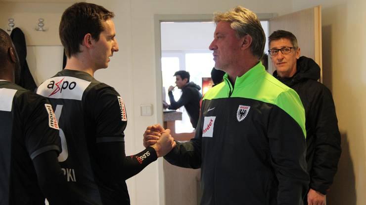 Trainer Marco Schällibaum klatscht vor dem Verlassen der Garderobe mit jedem einzelnen Spieler ab, hier mit Captain Sandro Burki