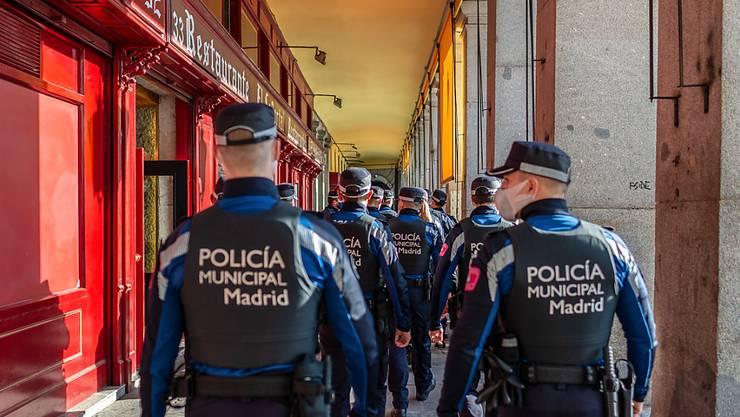 Eine Gruppe Polizisten mit Masken ist in der Stadtmitte im Einsatz. Zur weiteren Eindämmung der Corona-Pandemie riegelt sich Madrid zwischen dem 4. und dem 13. Dezember ab. Foto: Diego Radamã©s/Zuma Press/dpa