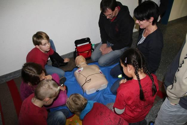 Kinder zeigen gekonnt den Eltern, wie ein Defigerät eingesetzt wird.