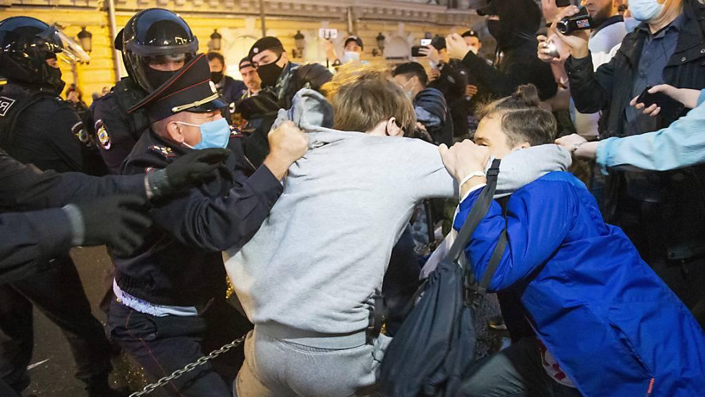 Polizeibeamte stoßen mit Demonstranten fest zusammen. Hunderte Menschen haben auf dem zentralen Puschkin-Platz gegen die umstrittenen Verfassungsänderungen protestiert, die vor rund zwei Wochen in Kraft getreten sind. Das neue Grundgesetz erweitert die Machtbefugnisse von Putin und ermöglicht ihm das Regieren bis 2036, sollte er wiedergewählt werden. Foto: Alexander Zemlianichenko/AP/dpa