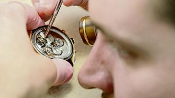 Arbeitnehmer wie dieser Uhrenarbeiter in La Chaux-de-Fonds erhalten wegen der Unternehmenssteuer weniger Lohn.