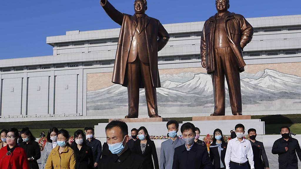 Menschen mit Maske besuchen den Mansu-Hügel, um vor dem Großmonument Mansudae, welches die zwei verstorbenen nordkoreanischen Machthaber Kim Il-sung (l) und Kim Jong-il zeigt, anlässlich des 75. Jahrestages der Gründung der Arbeiterpartei des Landes, Blumen niederzulegen. Foto: Cha Song Ho/AP/dpa