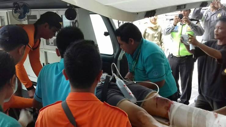 Rettungshelfer versorgen einen verletzten Bootspassagier.