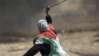 Ein Palästinenserin schleudert an der Gaza-Grenze zu Israel einen Stein.