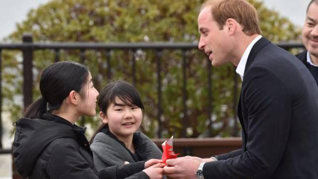 Mädchen überreichen Prinz William einen Kranich