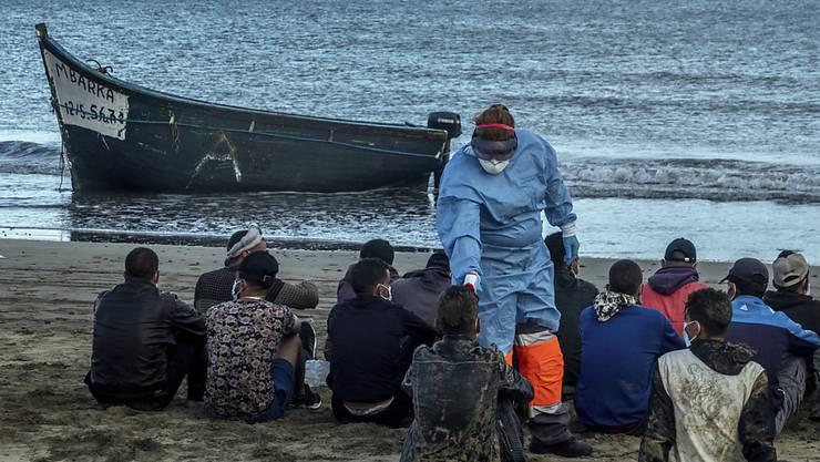 ARCHIV - Bei Migranten aus Marokko wird die Temperatur messen, nachdem sie mit einem Holzboot an der Küste von Gran Canaria angekommen sind. Foto: Javier Bauluz/AP/dpa