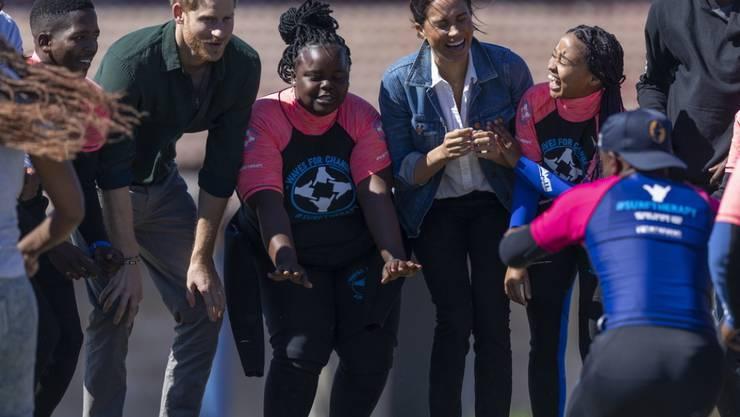 Prinz Harry (Dritter von links) und seine Frau Meghan (Dritte von rechts) haben am zweiten Tag ihrer Afrikareise zusammen mit Surflehrern am Monwabisi-Strand getanzt - für einen guten Zweck. Die Surflehrer arbeiten für eine Hilfsorganisation, die Kinder in den nahen Townships unterstützen.