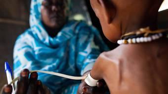 Den Menschen in der Krisenregion Darfur fehlt es praktisch an allem: Eine Pflegerin untersucht ein unterernährtes Kind in einem Spital. (Archiv)