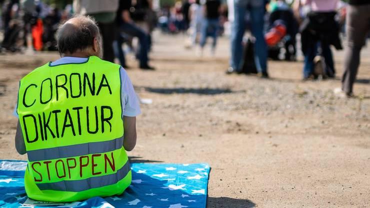 Ein Teilnehmer trägt bei einer Kundgebung der Initiative «Querdenken 711» in Stuttgart eine Warnweste mit der Aufschrift «Corona Diktatur stoppen».