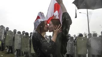 Zwei Frauen küssen sich unter den weiss-rot-weissen Farben der weissrussischen Demokratieaktivisten in Minsk.
