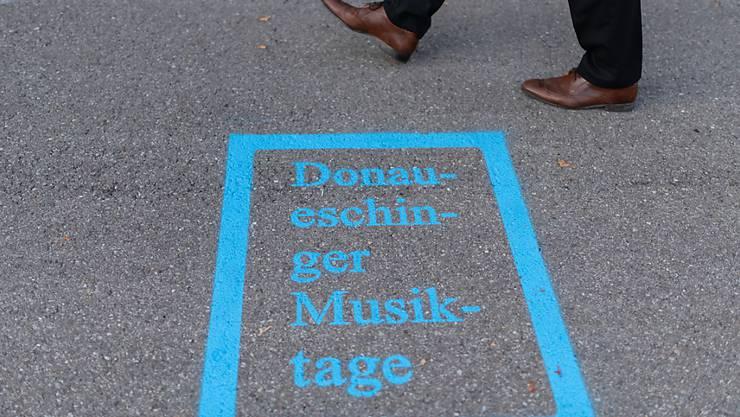 ARCHIV - Ein Mann läuft am Logo der Donaueschinger Musiktage vor der Donauhalle vorbei. Die Donaueschinger Musiktage sind nach Angaben der Veranstalter das weltweit älteste und renommierteste Festival für Neue Musik. Foto: Patrick Seeger/dpa