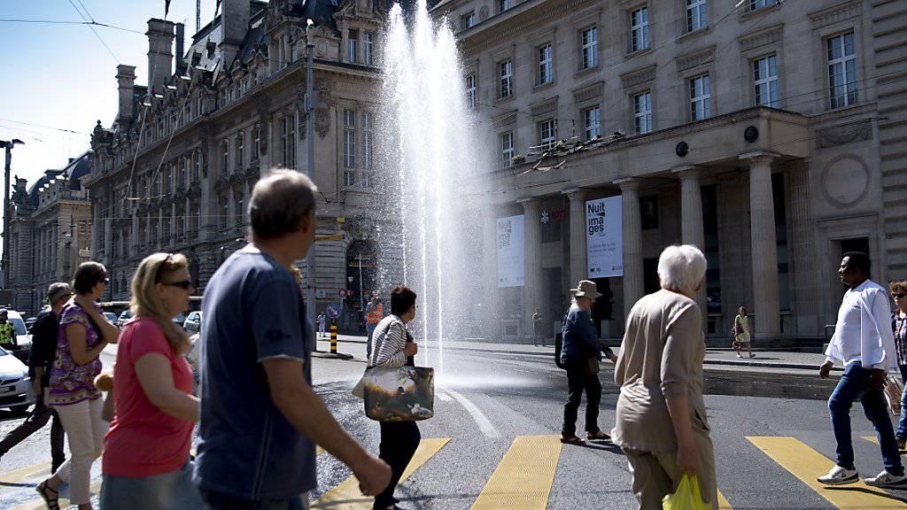 Die Passanten staunen am Mittwoch, dass bei der Place Saint-François drei Fontänen aus dem Boden schiessen. Der Verkehr wird durch die Springbrunnen nicht gestört, wie die Veranstalter versichern.