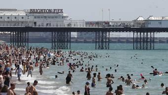 Menschen strömen bei schönem Wetter in Massen an den Strand von Brighton. Foto: Alastair Grant/AP/dpa