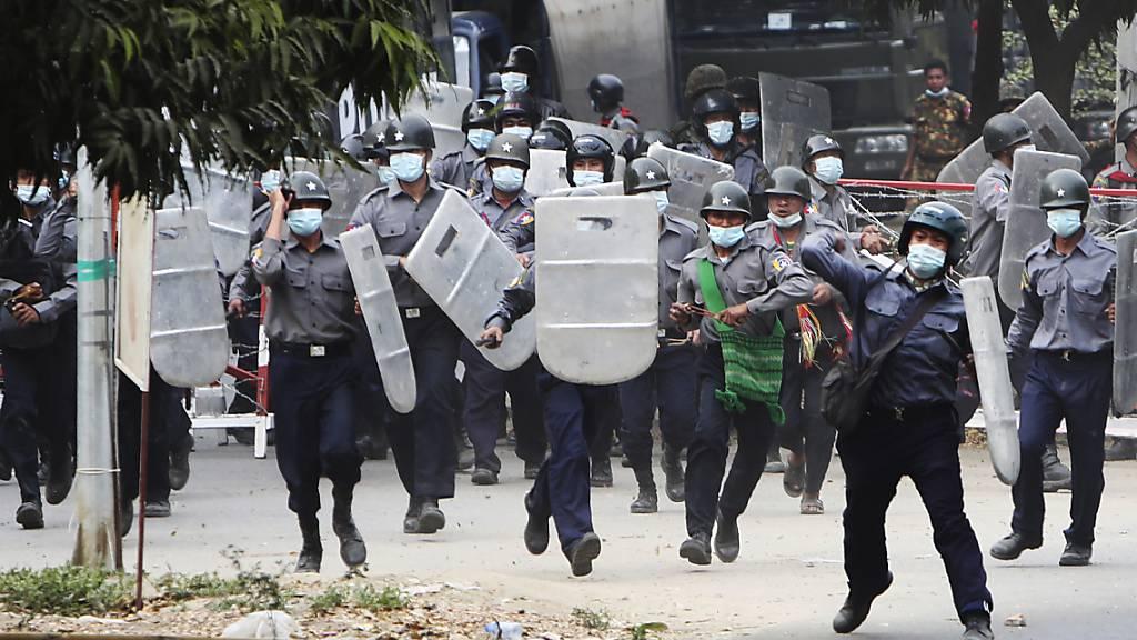 Polizisten stürmen auf Demonstranten zu, um sie zu vertreiben.