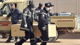 Algerische Feuerwehrleute beim Bergen einer Leiche aus der Gas-Anlage