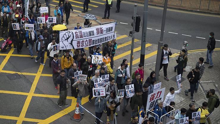 """Tausende fordern in Hongkong Aufklärung über den Verbleib von fünf Mitarbeitern eines chinakritischen Verlags. """"Nein zu politisch motivierten Entführungen!"""", heisst es auf den Plakaten."""