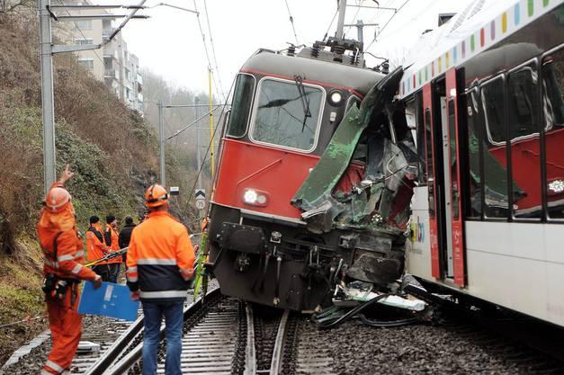 Einsatzkräfte stehen bei den zusammengestossen Zügen