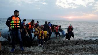 Syrische Flüchtlinge landen mit ihrem Schlauchboot an der Küste der Ferieninsel Lesbos.Thanassis Stavrakis/keystone