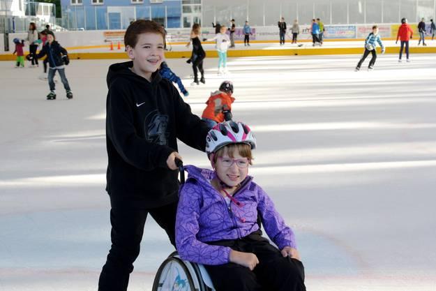 Leonie wird von Laurin über die Eisfläche geschoben. Die 9-Jährige ist glücklich, die Eishalle Weihermatt nicht mehr nur als Zuschauerin zu besuchen.