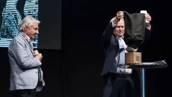Regierungsrat Paul Winiker enthüllt das Kunstobjekt, das Teil des Preises ist. Preisträger Emil Steinberger schaut gespannt zu. Bild: Pius Amrein  (Luzern, 29. April 2019)