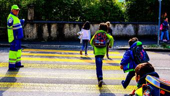 Bis die provisorische Fussgängerüberführung steht, sorgt ein Lotsendienst dafür, dass die Kindergärtner und Primarschüler sicher über die Strasse kommen. dka