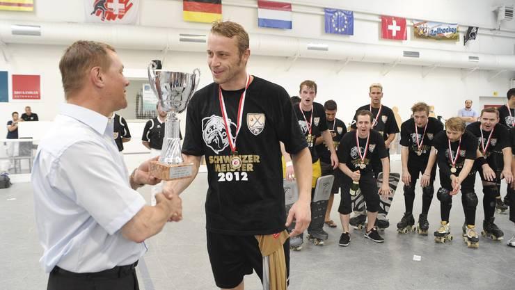 Captain Tobias Mohr nimmt den Meister-Pokal entgegen.