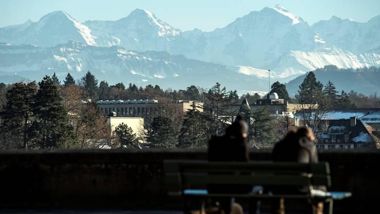 Sonnenanbeter geniessen die Aussicht mit Eiger, Moench und Jungfrau, in Bern. (KEYSTONE/Peter Schneider)