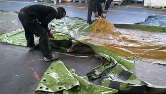 Zwei Mitarbeiter beim Zuschneiden alter LKW-Planen, dem Material der FREITAG-Taschen (Archiv)