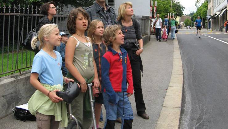 Gespannte Aufmerksamkeit: Teilnehmende am Hörspaziergang beobachten eine Darbietung an der Bäderstrasse.