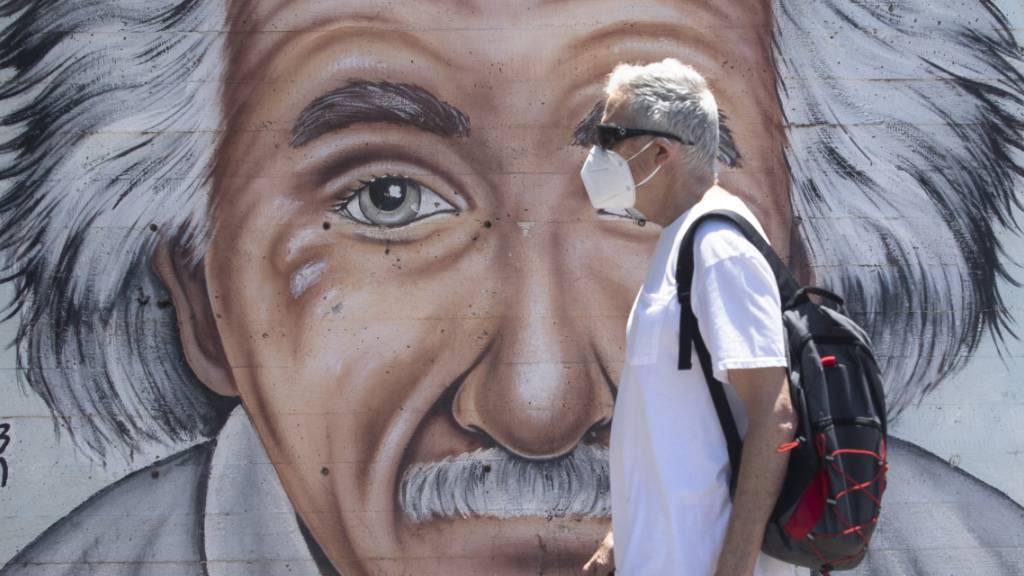 Ein israelischer Mann, der einen Mund- und Nasenschutz trägt, geht an einem Wandbild vorbei, das Albert Einstein zeigt. Zu Beginn der weltweiten Corona-Pandemie galt Israel vielen als leuchtendes Beispiel für eine rasche und erfolgreiche Eindämmung. Doch inzwischen steht das Mittelmeerland schlechter da als die meisten europäischen Länder, ein zweiter Lockdown erscheint unausweichlich. Foto: Sebastian Scheiner/AP/dpa