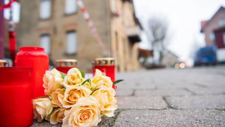 Am Tag nach den tödlichen Schüssen in Rot am See auf 6 Menschen liegen Blumen und Kerzen vor dem Tatort.