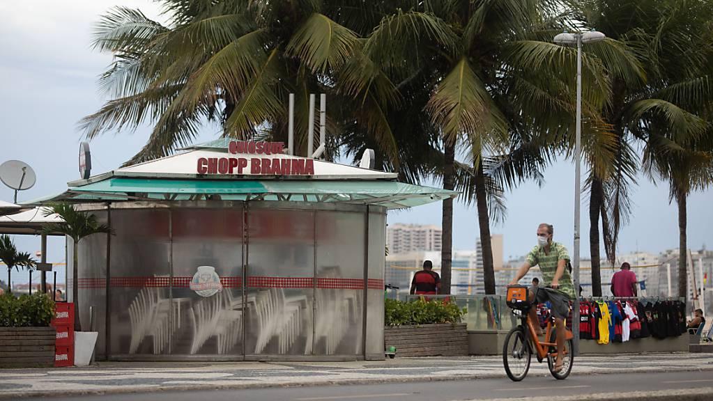 Ein Mann fährt mit dem Rad an einem geschlossenen Kiosk am brasilianischen Strand Copacabana vorbei. (Archivbild)