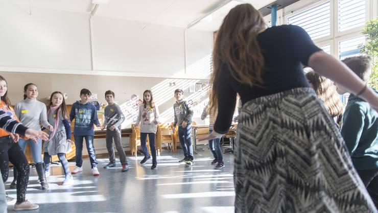 17 Schülerinnen und Schüler der fünften Klasse machen die Schritte der Tanzlehrerin nach.