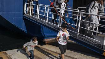 Migranten mit Mundschutz kommen im Hafen von Piräus in der Nähe von Athen an. Die griechischen Behörden verlegen etwa 180 Migranten auf das Festland, um die überfüllten Verhältnisse im Lager Moria auf der Insel Lesbos zu erleichtern. Foto: Petros Giannakouris/AP/dpa