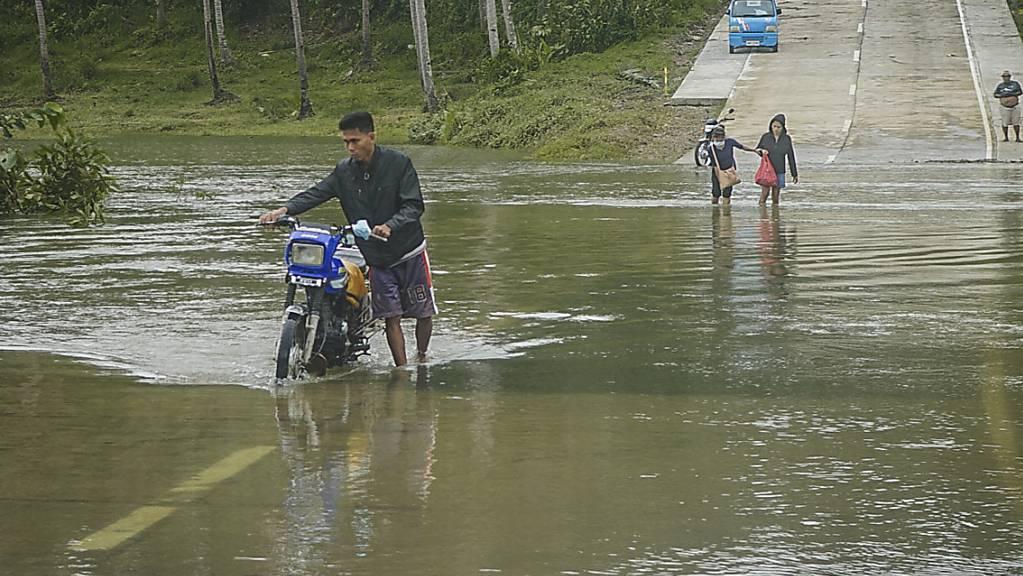 Bewohner überqueren eine überflutete Straße auf den Philippinen. Die Überflutungen wurden durch den Regen des Taifuns «Surigae» verursacht, der bisher mindestens sieben Menschenleben gefordert hat. Foto: Uncredited/AP/dpa