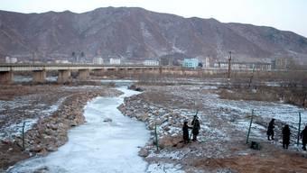 Chinesische Polizisten errichteten entlang dem Grenzfluss im Dezember in Tumen einen Grenzzaun zu Nordkorea (im Hintergrund).Key