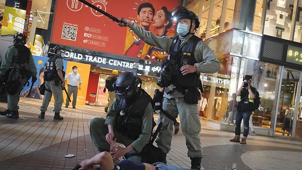 Bereitschaftspolizisten verhaftet eine Demonstrantin während einer Demonstration im Einkaufsviertel Causeway Bay. Foto: Vincent Yu/AP/dpa