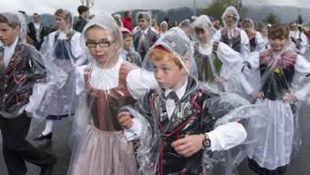 Kinder des Gastkantons Obwalden schützen die Trachten mit Pelerinen