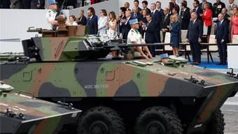 US-Präsident Trump (im Hintergrund) an einer Militärparade in Paris.