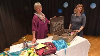Elisa Landis (links) und Anna Hoyer-Bühler haben farbige Gegenstände als Symbole für die einzelnen Chronikberichte in einen alten, braunen Koffer gepackt.
