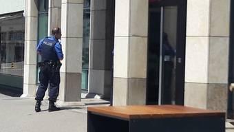 Polizist vor der UBS-Filiale in Wettingen, die am Mittag überfallen wurde.