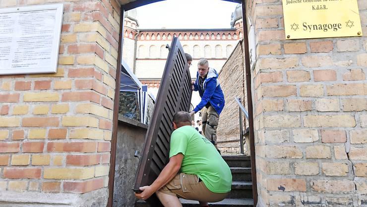 Tischlermeister Thomas Thiele hängt die Tür zum Grundstück der Synagoge aus. Foto: Hendrik Schmidt/dpa-Zentralbild/dpa