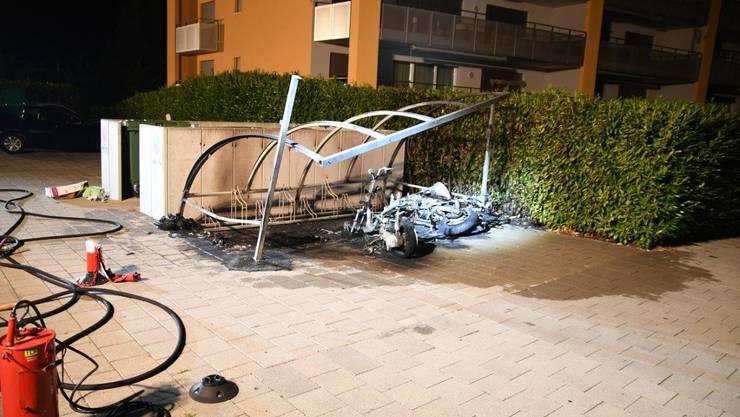In einem Fahrradunterstand bei einer Mehrfamilienhaussiedlung in Buchs brach ein Brand aus. Der Schaden ist beträchtlich: Das Feuer zerstörte den Unterstand und zwei darunter eingestellte Motorräder.