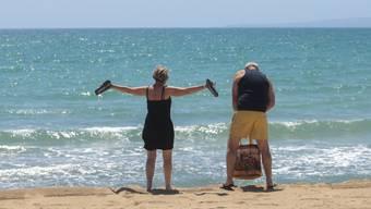 Deutsche Touristen stehen am Strand von Palma de Mallorca. Nach wochenlanger Corona-Pause ist am Montag erstmals wieder eine Maschine mit Urlaubern aus Deutschland auf Mallorca gelandet. Foto: Joan Mateu/AP/dpa